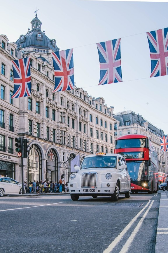 A street in London with the British flags, a white taxi and a red doubledecker bus