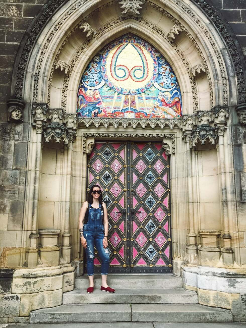 a female english teacher who lives abroad in prague posing in front of a beautiful church door