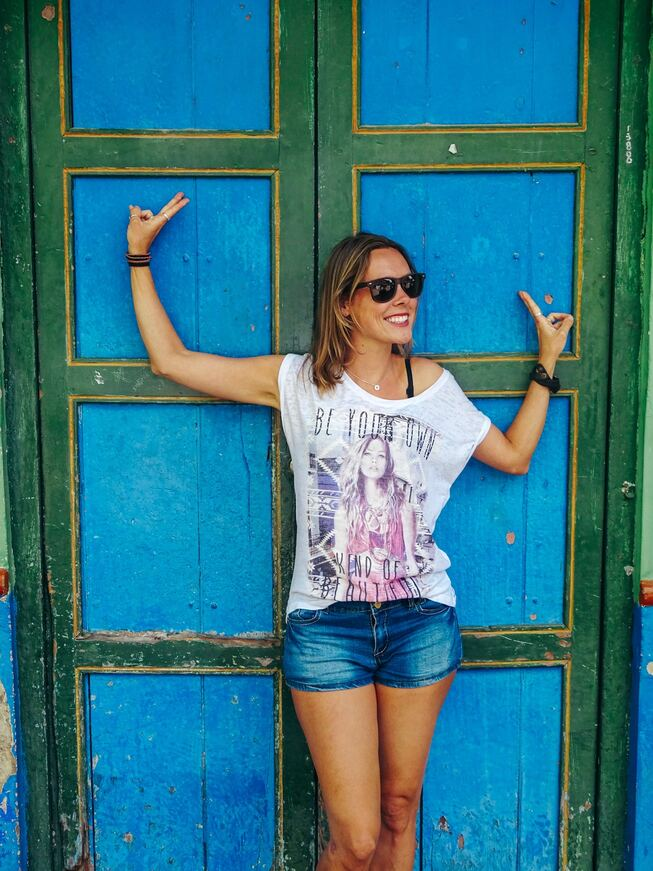 Solo female traveler posing in front of blue and green wooden doors in Cartagena, Colombia