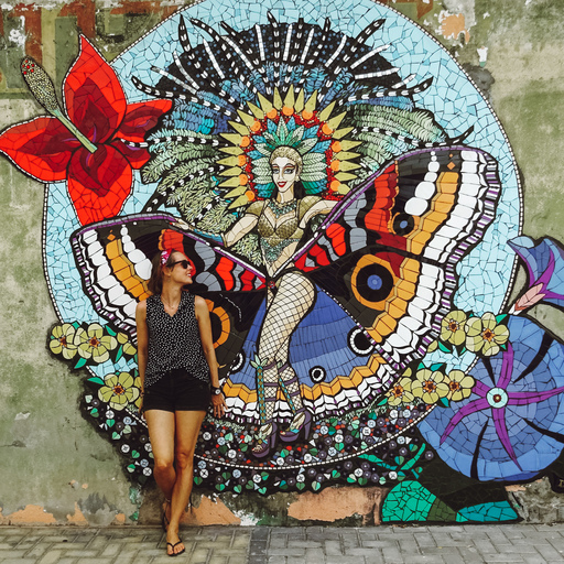 A solo female traveler posing in front of a wall mural or a woman with butterfly wings