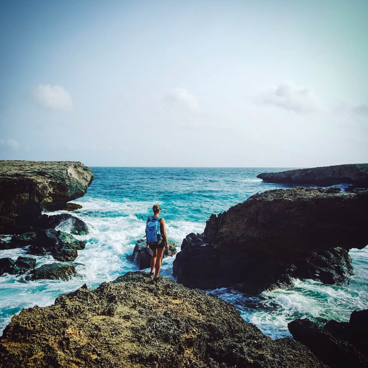 A woman standing on the rocks looking out over the horizon on a rocky coast in Aruba