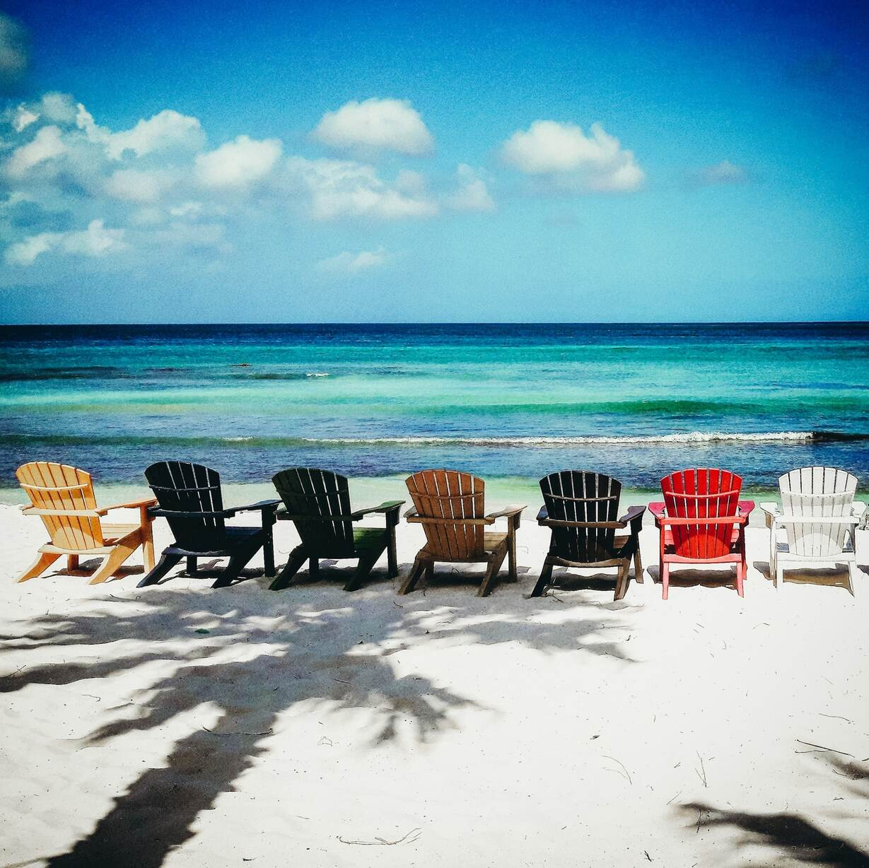 7 colorful wooden beach chairs set up in the sand on the beach in Aruba
