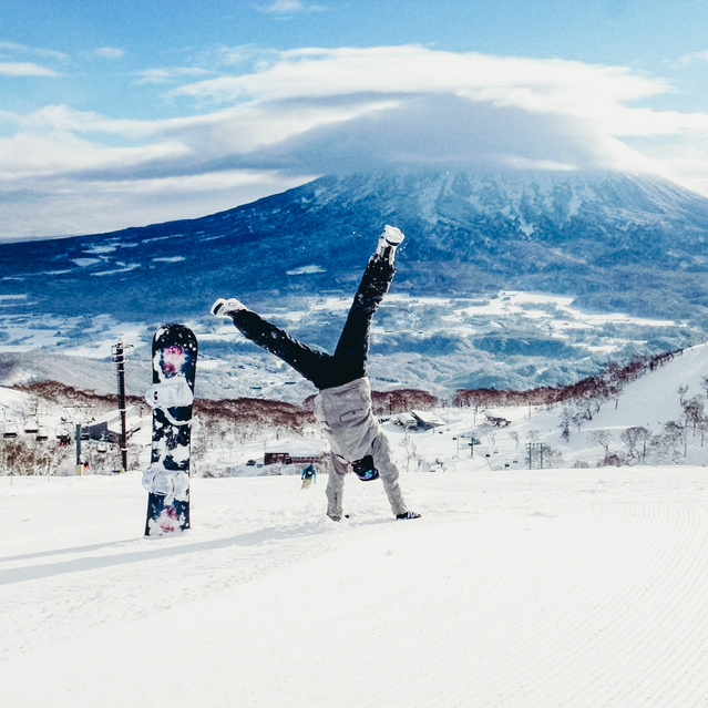 A foreigner working a ski season in Japan doing a handstand in the snow
