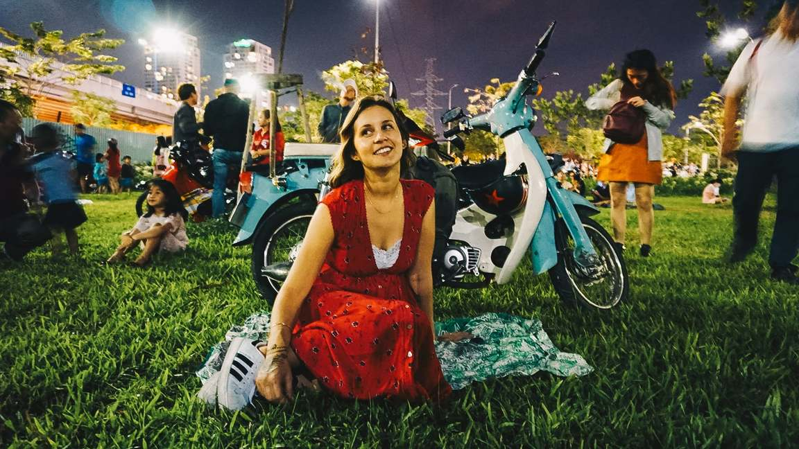 girl sitting with blue honda cub in the park at night