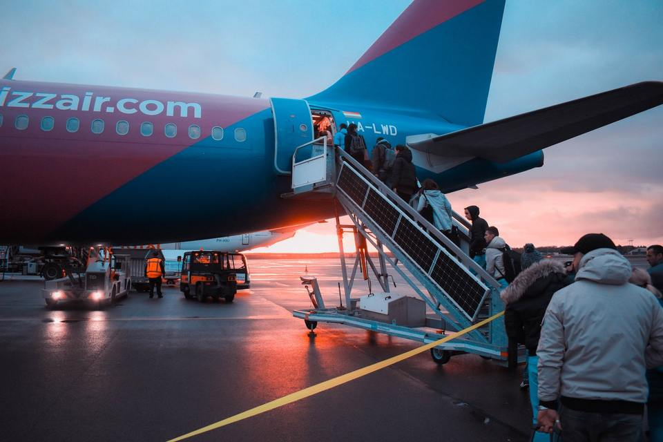 Line of people boarding a flight outside at sunrise