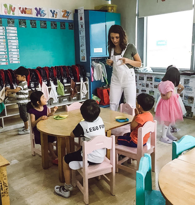 An English teacher in Seoul, Korea in her classroom interacting with her young students