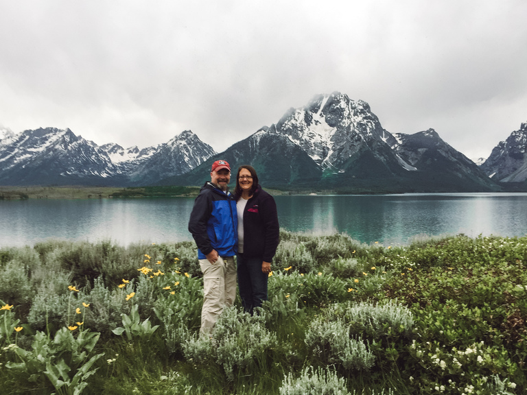 A couple posing in front of a lake and snowy mountains in Grand Teton National Park