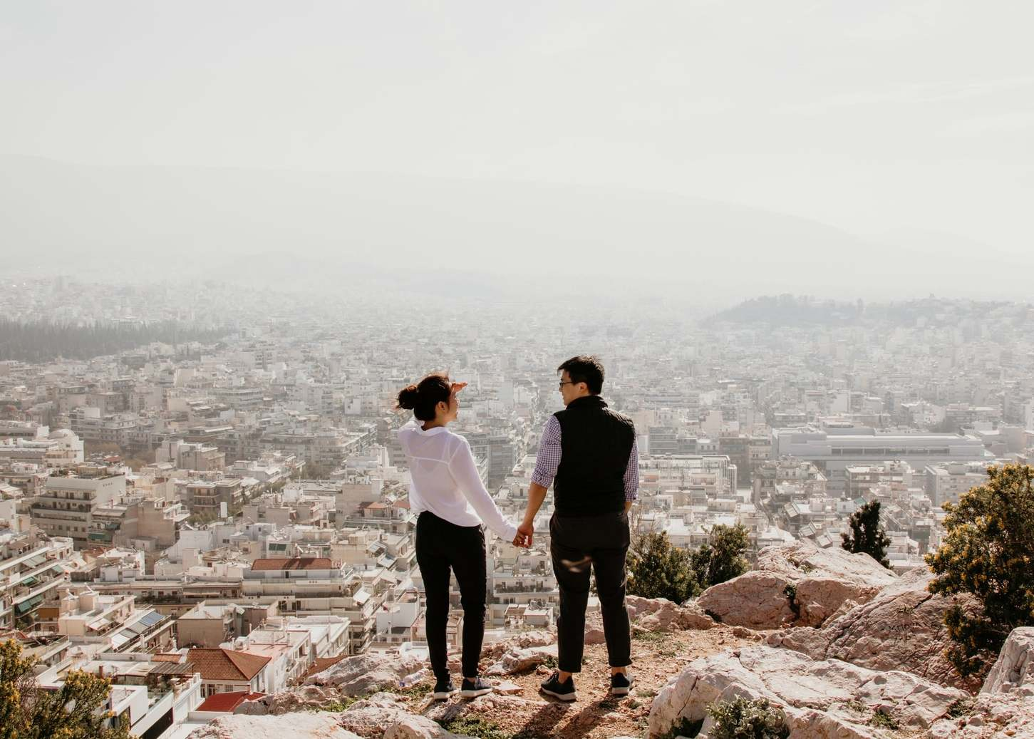 A couple, holding hands, overlooking a city from a look out point