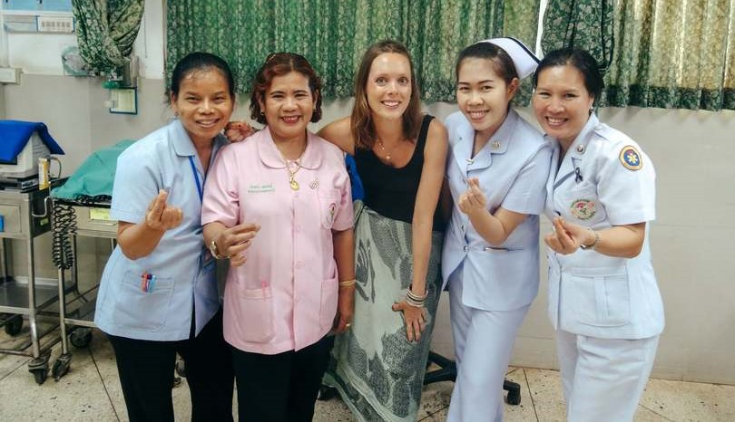 An international travel nurse posing with other nurses