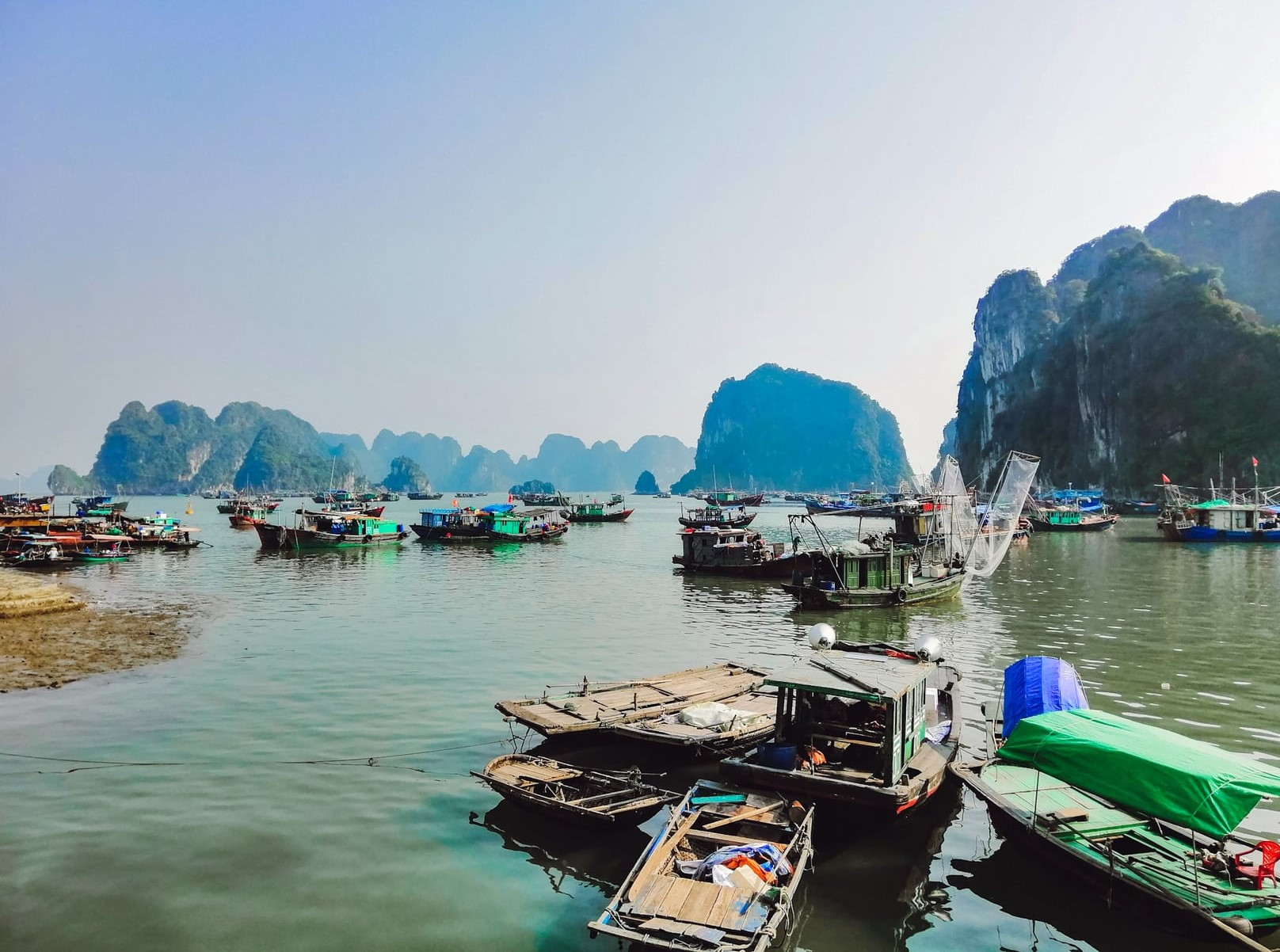 A clear afternoon in Ha Long Bay with the limestone rocks and bamboo boats