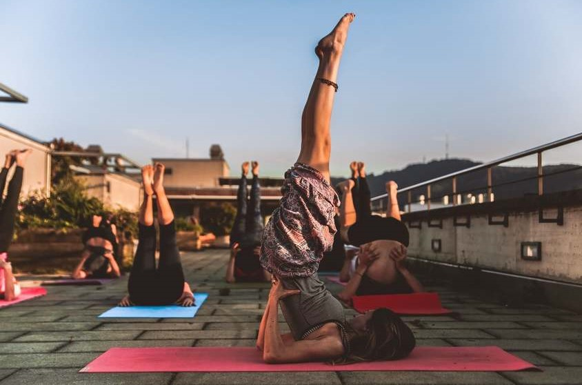 Yoga teacher offering a class on a rooftop abroad
