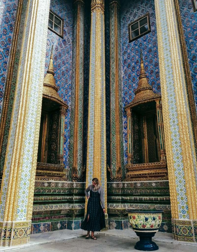 A foreigner living in Bangkok posing in the corner of an ornate blue and gold temple