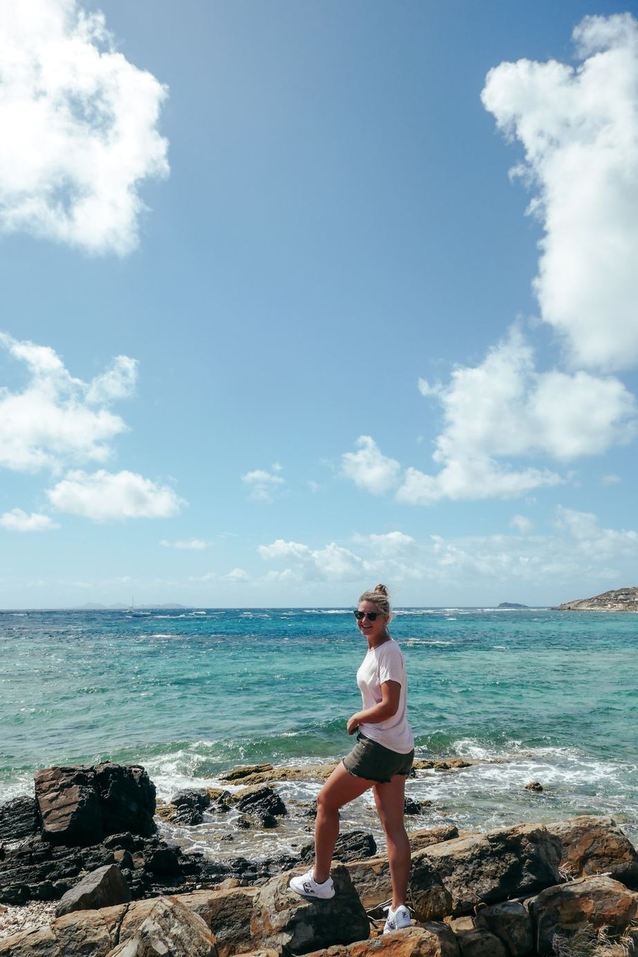A young woman standing on rocks over the ocean smiling at the camera in Sint Maarten