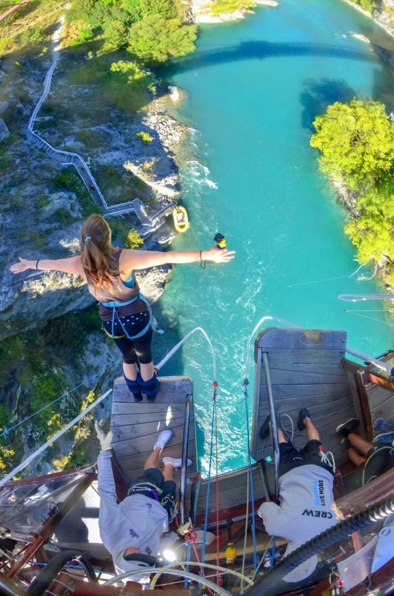 A girl about to jump off the platform to go bungee jumping over a lake in New Zealand