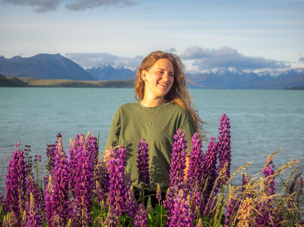 female posing behind purple flowers and in front of a lake and mountain backdrop in New Zealand