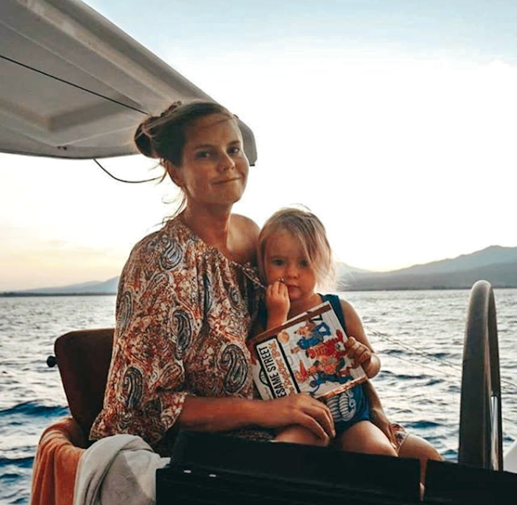 Mom and 3-year old daughter reading a book on their sailboat