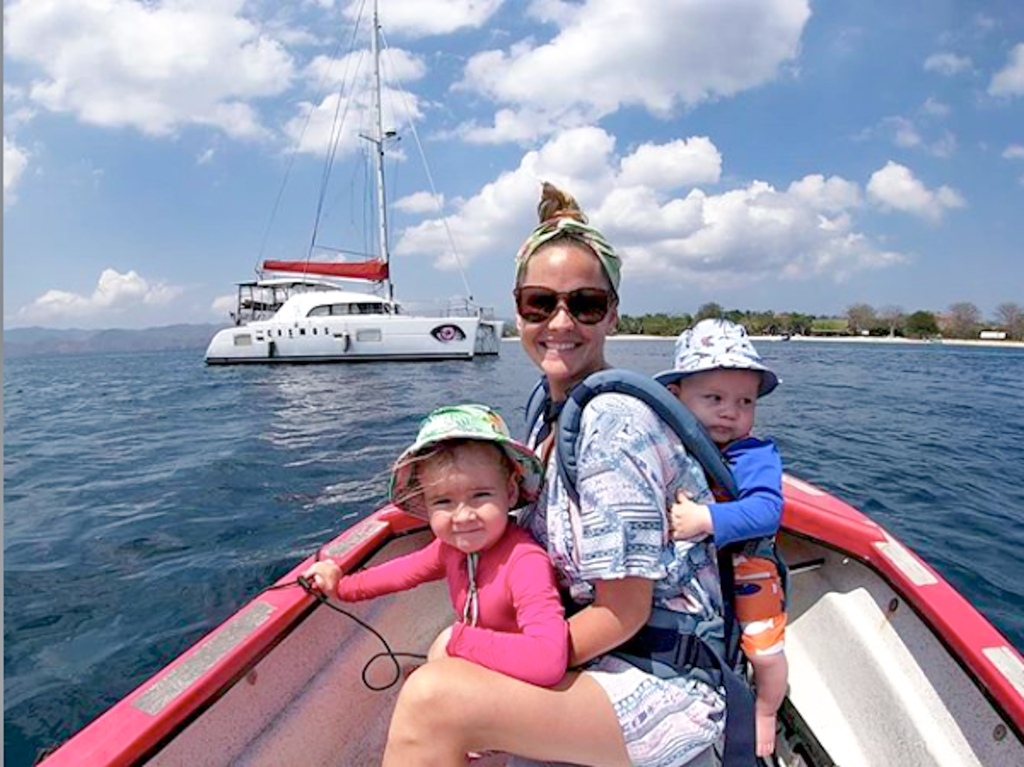 A happy family on a dingy boat, with their sailboat in the background
