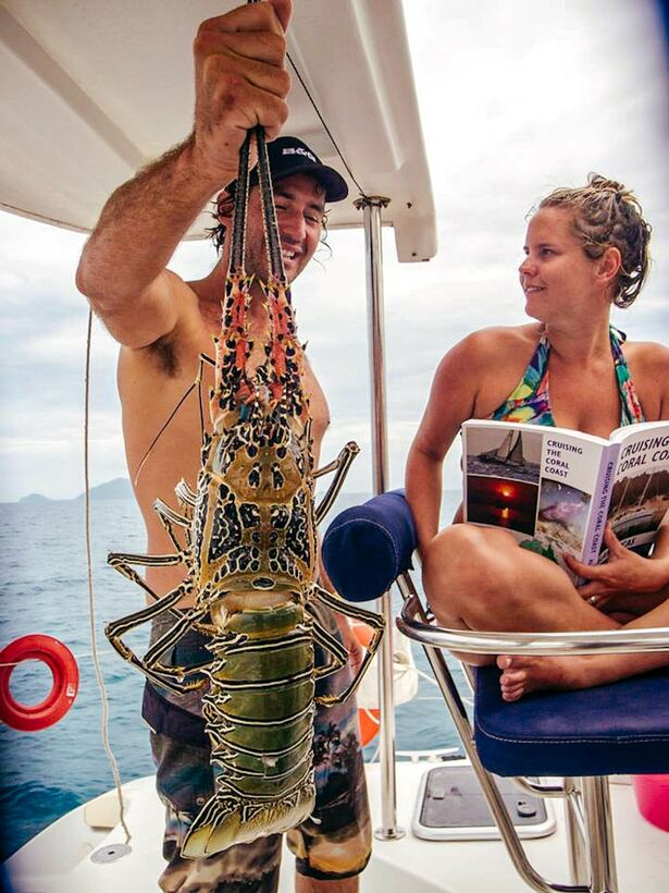 Man and woman on sailboat with freshly caught lobster