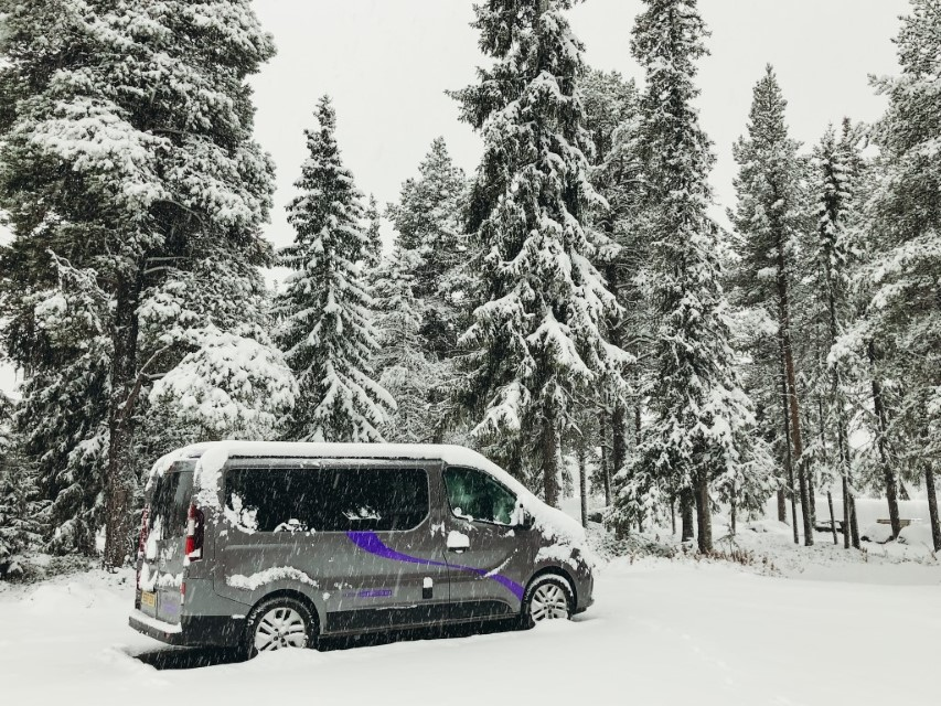 A camper van parked in the forests during a big snow storm