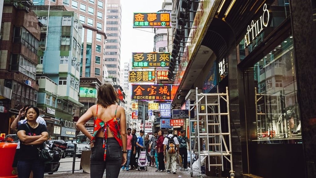 A female tourist standing on the sidewalk in Hong Kong looking at the busy street and neon signs