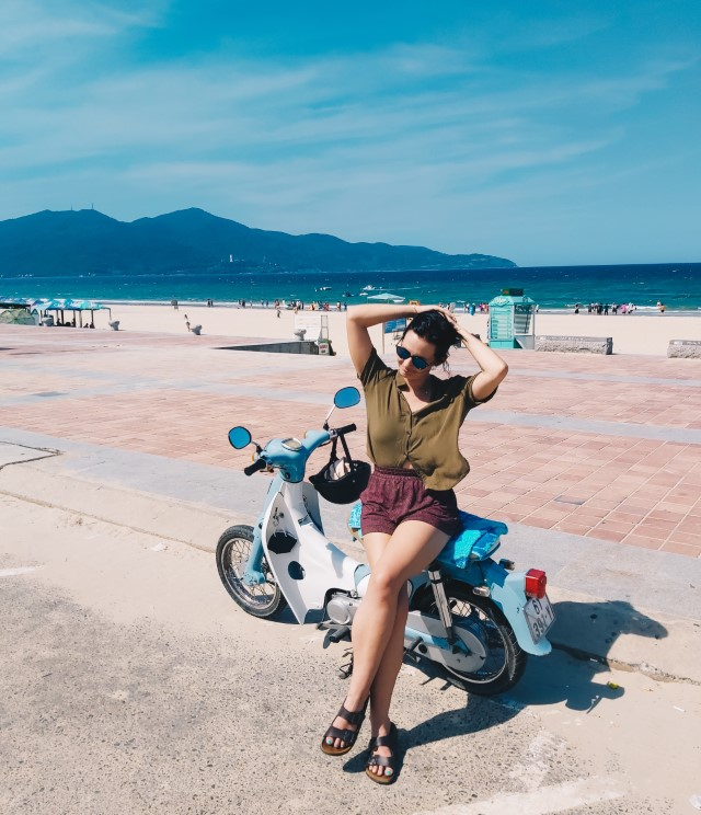 A foreign woman sitting on her motorbike on the coast in Vietnam with the beach and mountains behind her