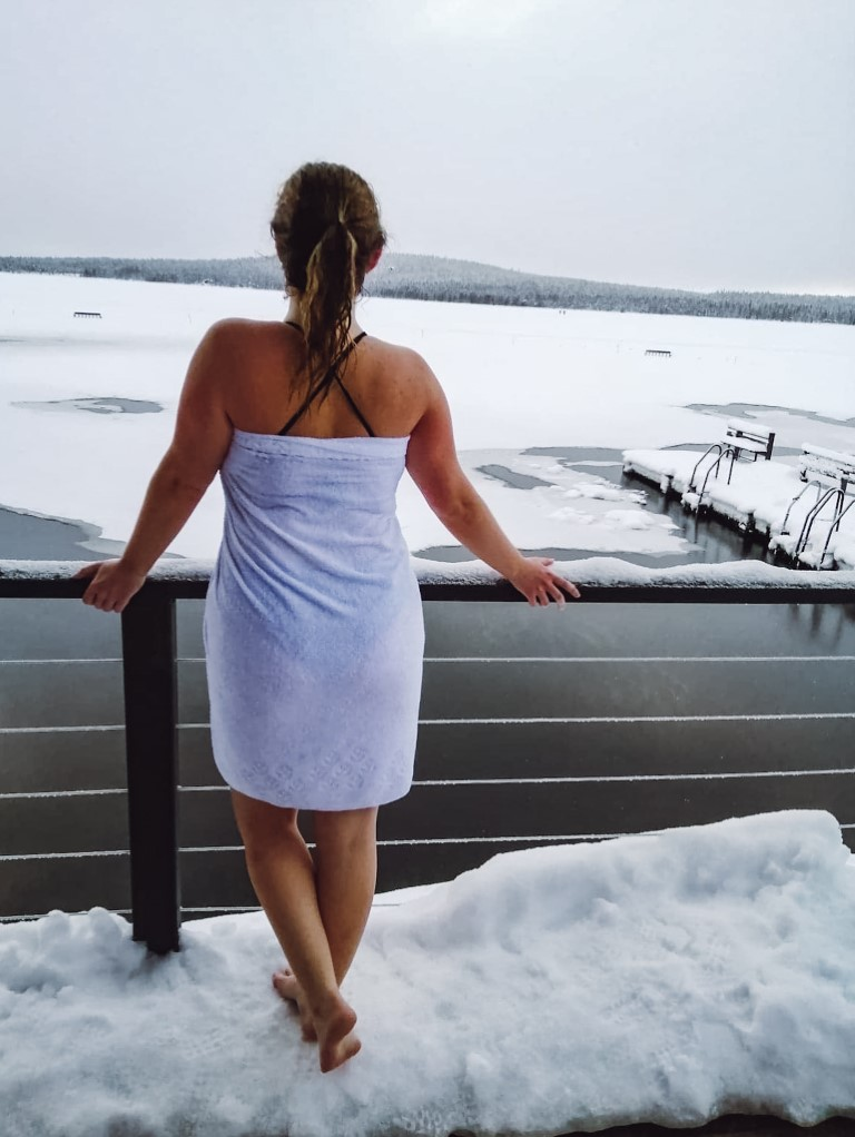 A woman wearing a swimsuit and towel standing outside in the snow in Lapland
