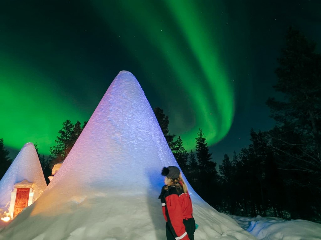 A woman at a Finnish resort looking up to the sky to see green aurora, or Nothern Lights.