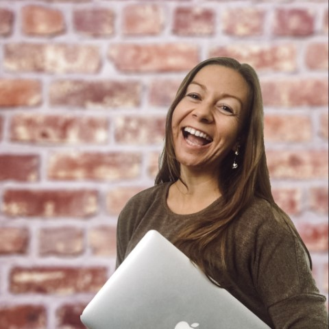 A very happy woman smiling to the camera holding her laptop in front of a brick wall