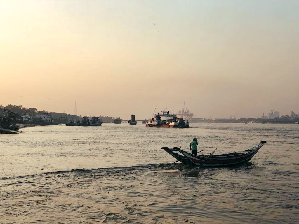 the yangon river at sunset with small fisher boats and bigger barges