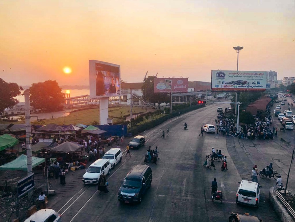Downtown Yangon at sunset with some cars and pedestrians crossing the street