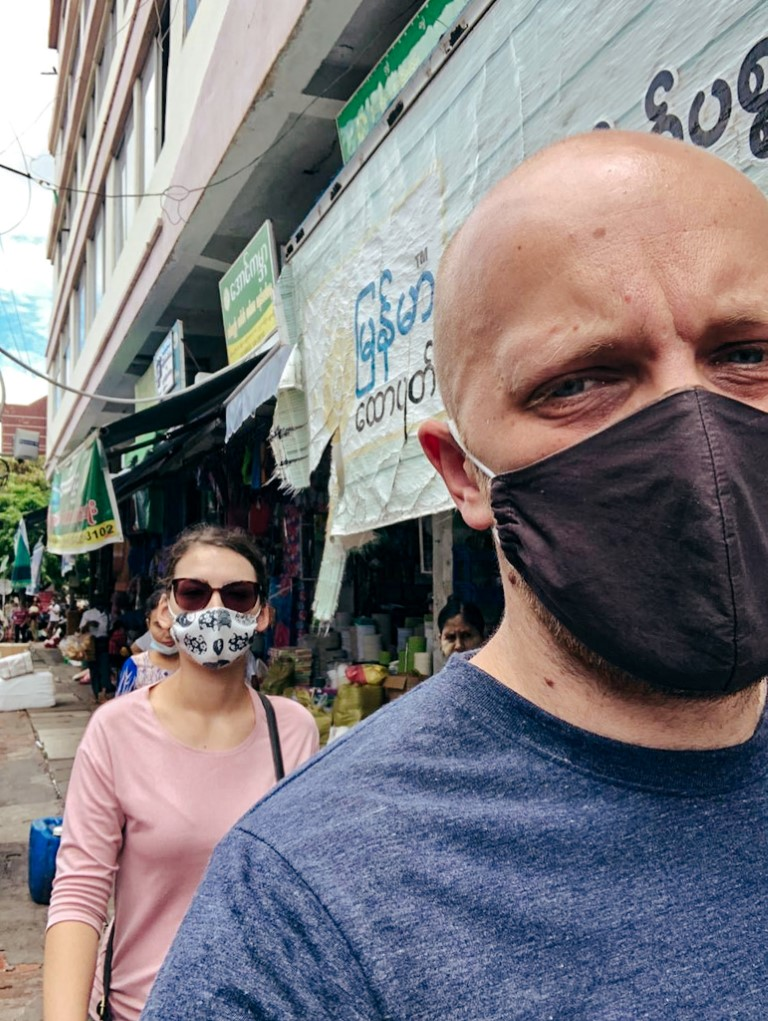 a foreign couple living abroad in myanmar during coronavirus, wearing masks, walking through the local market