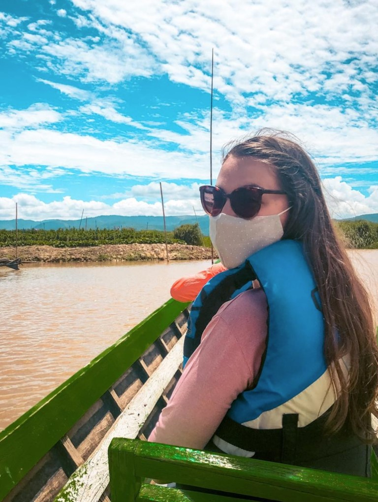 A female expat living abroad in Myanmar, wearing her face mask on a boat trip.