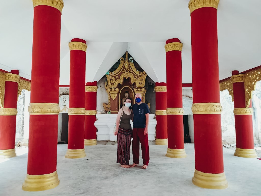 A foreign couple living in Myamar, exploring local temples without any tourists, wearing a face mask and no shoes