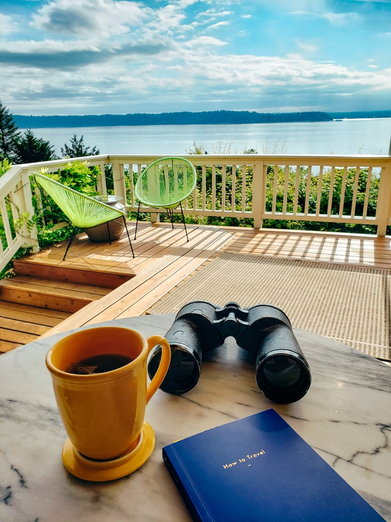 a beautiful view of a lake on a sunny day with a pair of binoculars, a small travel book and a coffee on a table outside