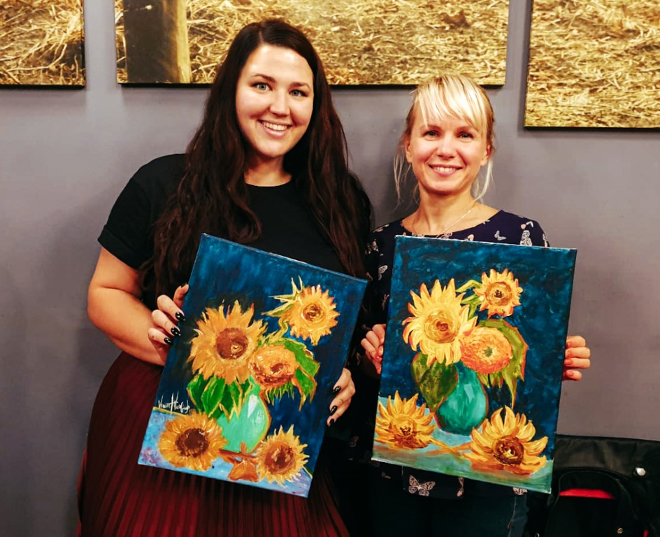 two women holding up their paintings of sunflowers on a fun night out