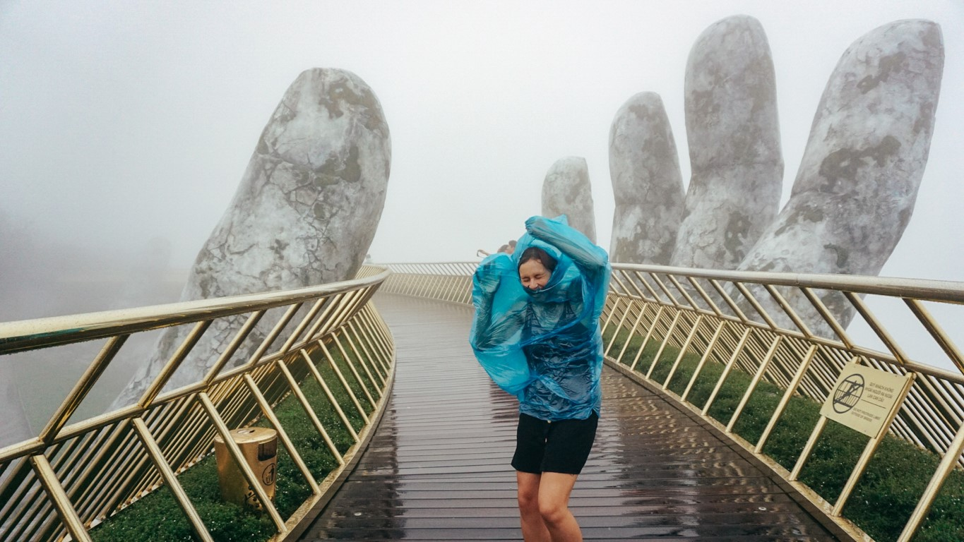 A woman on the golden hands bridge in Da Nang, Vietnam in a storm caught in her poncho