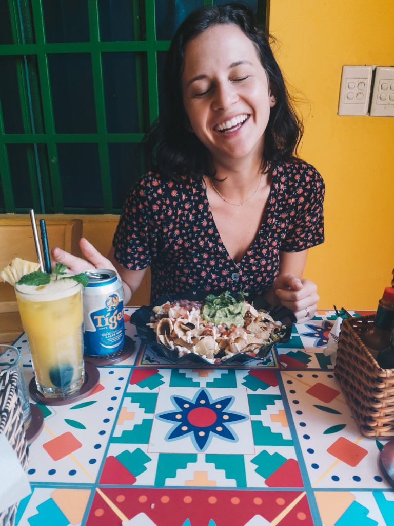 A woman closing her eyes and smiling at the camera ready to eat at a Mexican restaurant
