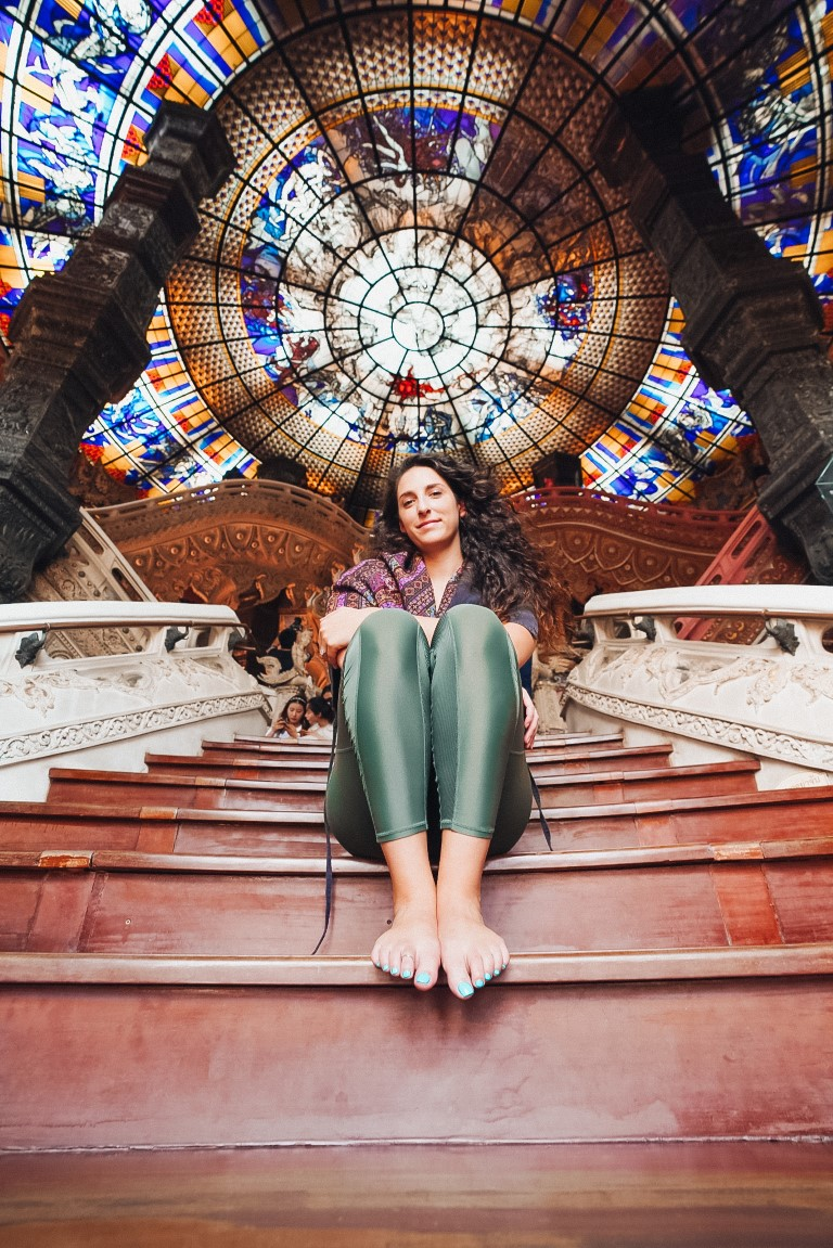 A woman sitting on the steps of a museum with a view of the stained glass roof above her
