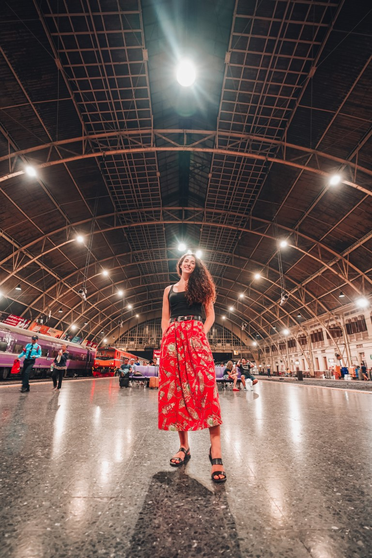 A woman wearing a long red skirt posing for the camera at a big, open train station