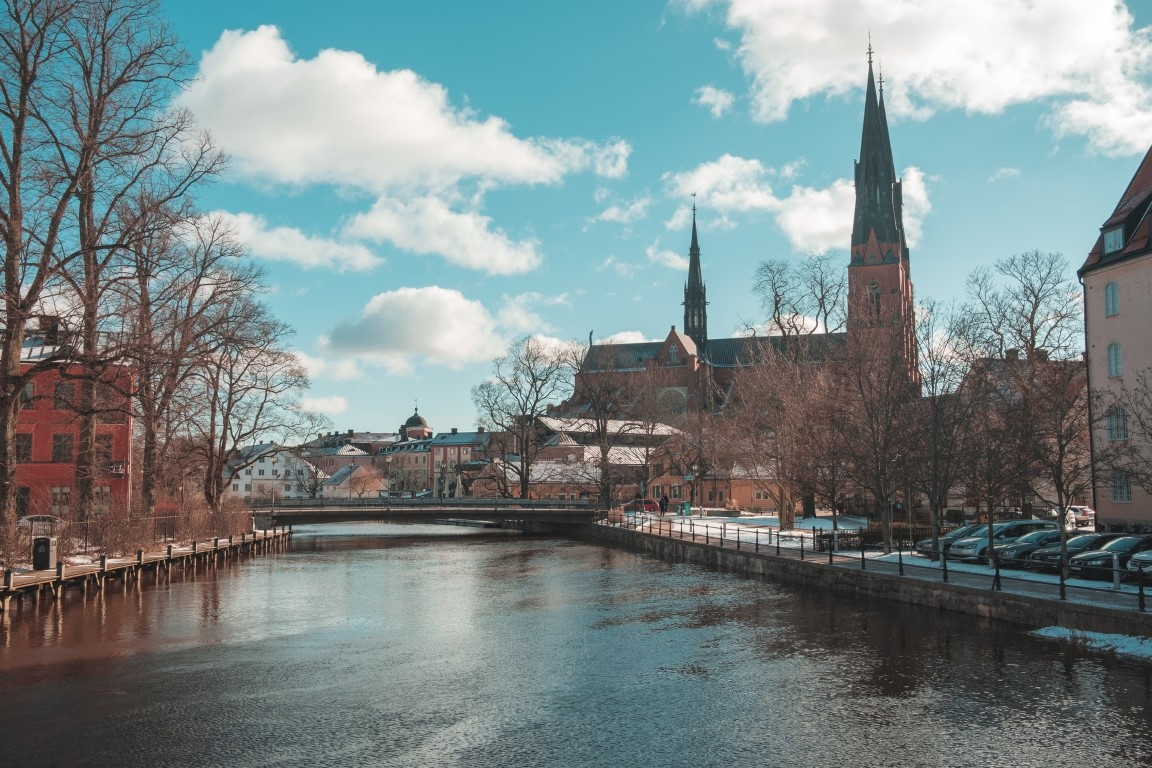Uppsala, Sweden view of the river with houses, trees and a church on the banks.