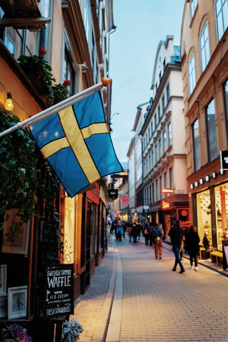 a quaint alley at dusk with people walking by and a Swedish flag in the forefront