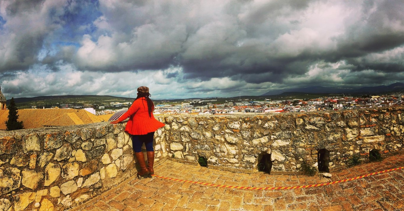 Solo woman looking out at a view point in Andalusia on a cloudy day