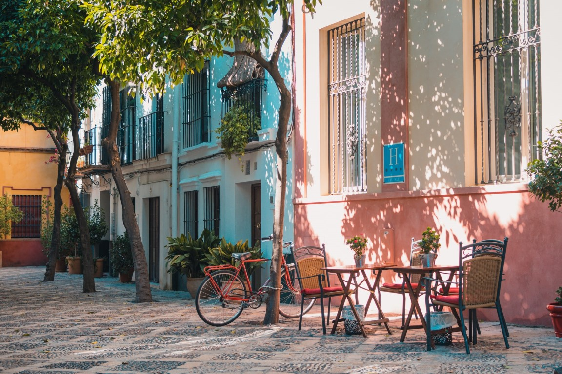 A colorful, empty street in Sevilla with an empty cafe table and a parked bicycle under the trees