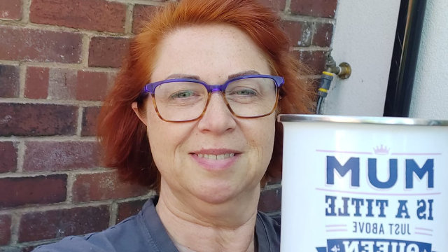 a mom wearing glasses holding a mug taking a selfie outside her house