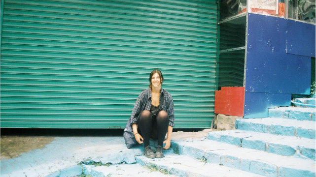 A solo female traveler sitting on a side alley smiling at the camera. Picture taken on film camera.
