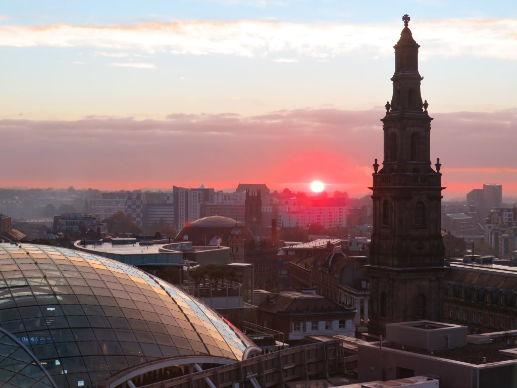 A rooftop view of a red setting sun over the city of Leeds, UK