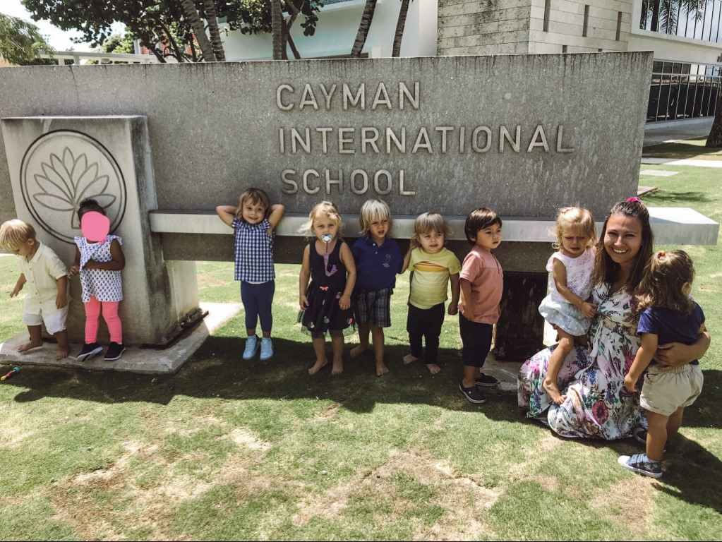 teacher posing with her young students in front of their school sign on the Cayman islands