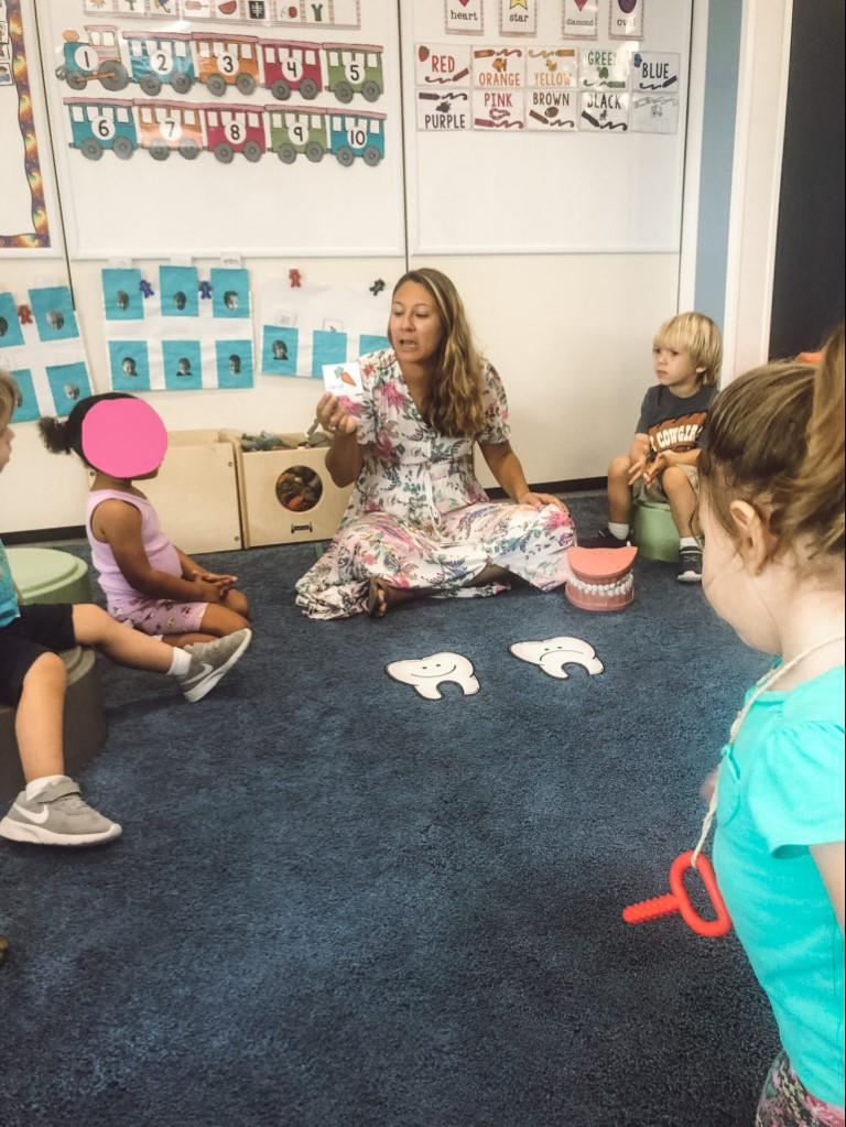 A teacher sitting on the floor with her students around her at an international school