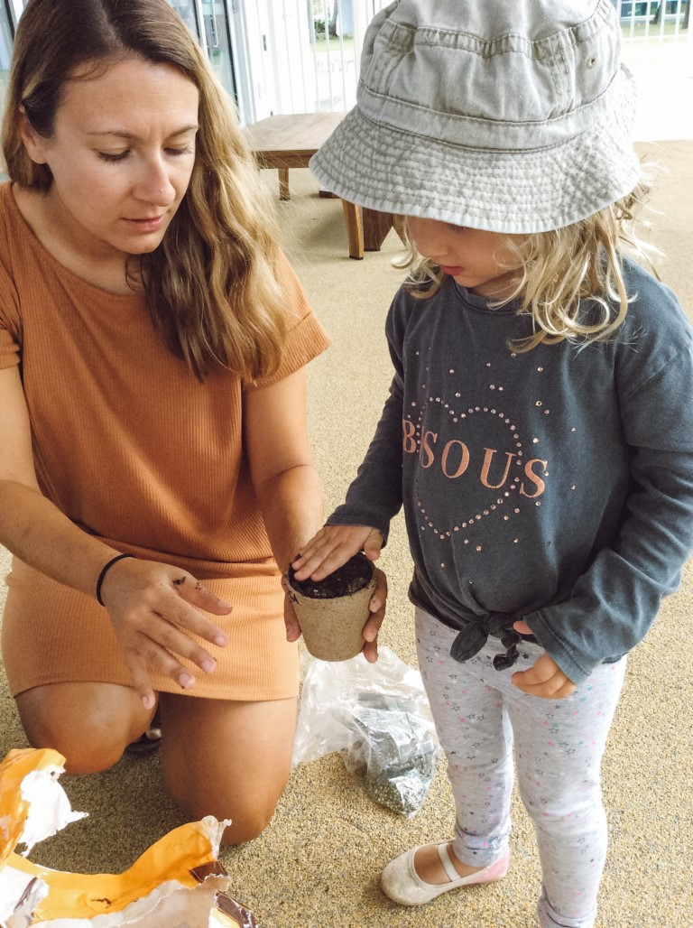 A teacher helping a young student put soil into a pot to plant some seeds