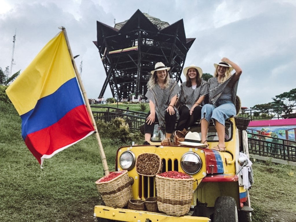 Three foreign women who live abroad in Colombia on a touristic trip outside of Medellin posing in a jeep with a Colombian flag